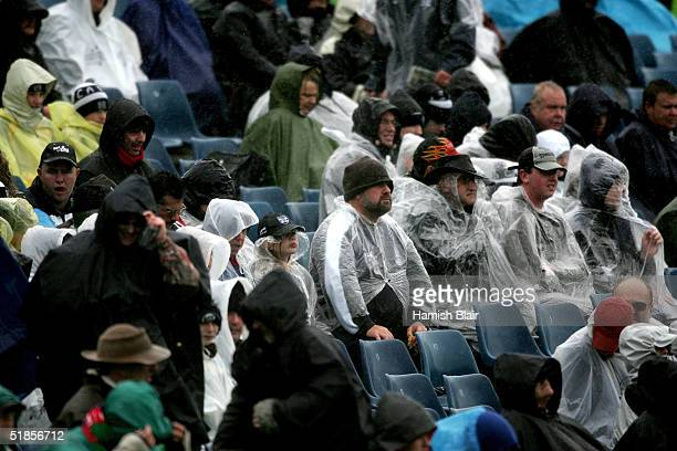 Fans in the crowd watch the match in the rain during the round 20 AFL match between the Geelong Cats and the Fremantle Dockers played at Skilled...
