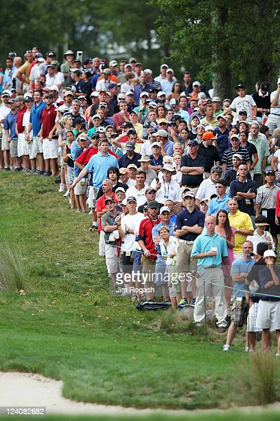 Fans in the gallery look down the 18th hole fairway towards the green during the final round of the Deutsche Bank Championship at TPC Boston on...