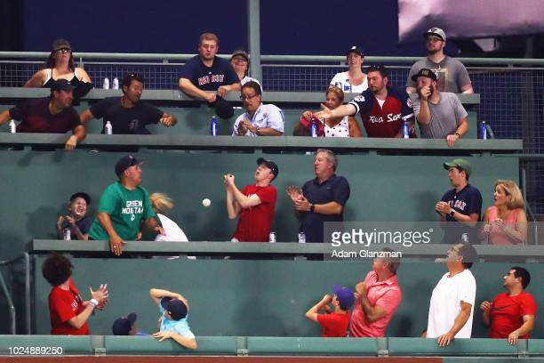 Fans in the Green Monster reach for a solo home run ball hit by Isaac Galloway of the Miami Marlins in the third inning of a game against the Boston...