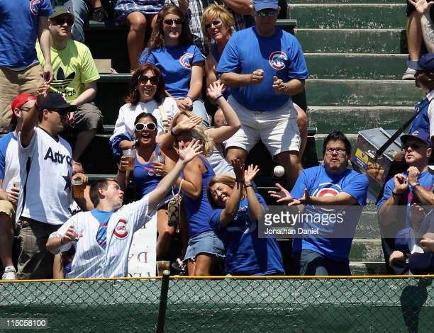 Fans in the left field bleachers try to catch a home run ball hit by Kouske Fukudome of the Chicago Cubs against the Houston Astros at Wrigley Field...