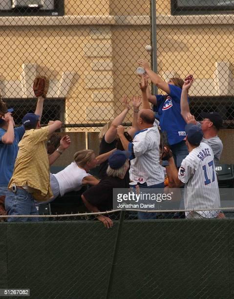 Fans in the left field bleechers scramble to catch a home run by Michael Barrett of the Chicago Cubs, the fifth Cubs home run of the game, in the...