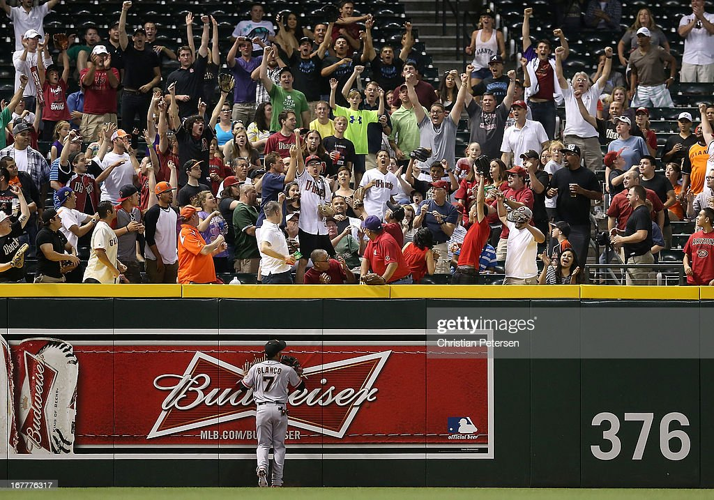 Fans in the outfield react after a home run hit by Eric Chavez (not pictured) of the Arizona Diamondbacks over outfielder Gregor Blanco #7 of the San Francisco Giants during the fourth inning of the MLB game at Chase Field on April 29, 2013 in Phoenix, Arizona.