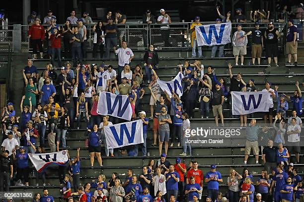 Fans in the right field bleachers hold 'W' flags after the Chicago Cubs beat the Cincinnati Reds at Wrigley Field on September 21 2016 in Chicago...