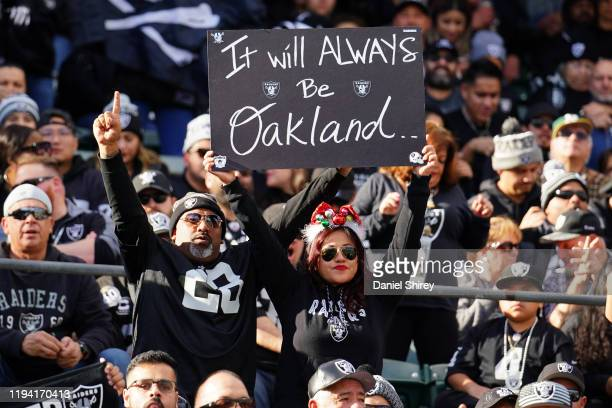Fans in the stands hold signs during the first half between the Oakland Raiders and the Jacksonville Jaguars at RingCentral Coliseum on December 15,...