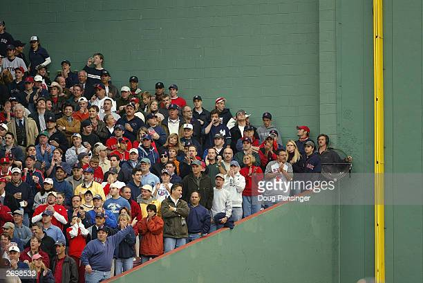 """Fans in the stands next to the """"green monster"""" the left field wall during Game five of the 2003 American League Championship Series between the..."""