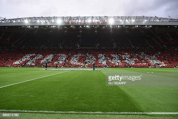 Fans in the stands spell out the name of Manchester United's English striker Wayne Rooney before kick off of the friendly Wayne Rooney testimonial...