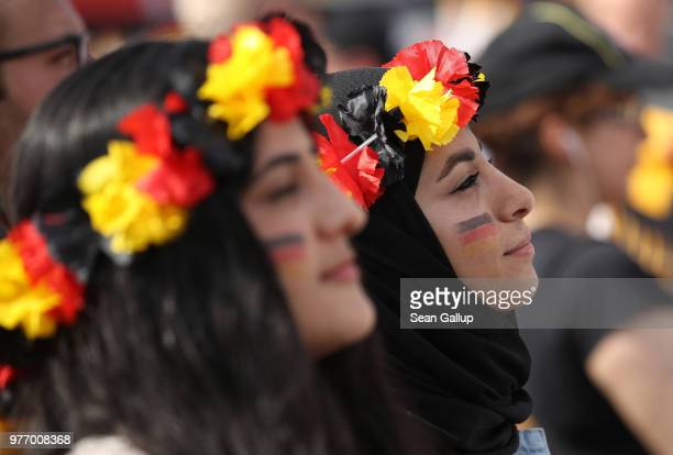 Fans including a young woman wearing a headscarf arrive at the Fanmeile public viewing area to watch the Germany vs Mexico 2018 FIFA World Cup match...