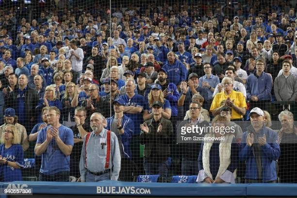 Fans including musician Geddy Lee salute the memory of the late Roy Halladay of the Toronto Blue Jays during a pregame ceremony on Opening Day during...