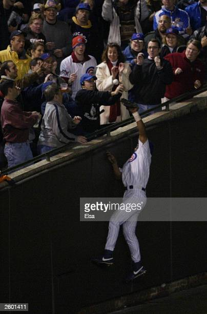 Fans interfere with outfielder Moises Alou of the Chicago Cubs on a ball hit by Luis Castillo of the Florida Marlins scoring two runs in the eighth...