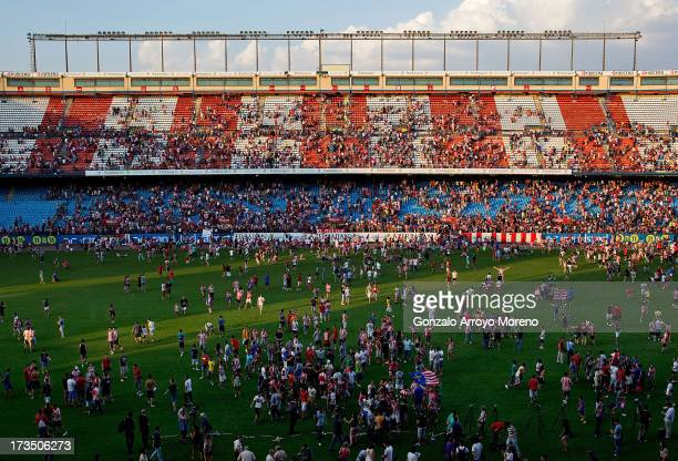 Fans invade the pitch after David Villa's presentation as a new Atletico de Madrid player at Estadio Vicente Calderon on July 15 2013 in Madrid Spain