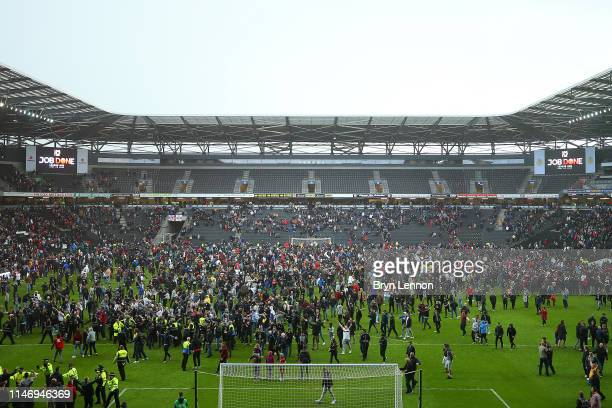Fans invade the pitch after the Sky Bet League Two match between Milton Keynes Dons and Mansfield Town at Stadium mk on May 04, 2019 in Milton...