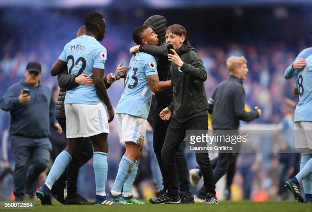 Fans invade the pitch and embrace Benjamin Mendy and Gabriel Jesus of Manchester City during the Premier League match between Manchester City and...