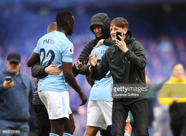 Fans invade the pitch and embrace Benjamin Mendy and Gabriel Jesus of Manchester City following the Premier League match between Manchester City and...