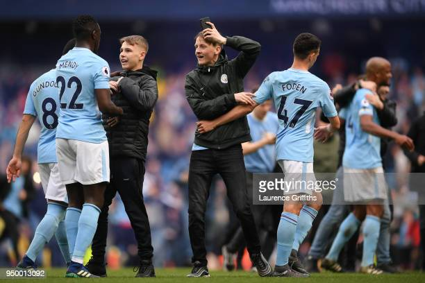 Fans invade the pitch and speak with Benjamin Mendy Gabriel Jesus and Phil Foden of Manchester City following the Premier League match between...