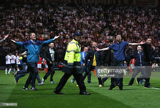 Fans invade the pitch at the final whistle of the Capital One Cup first round match between Preston North End and Blackpool at Deepdale on August 5...