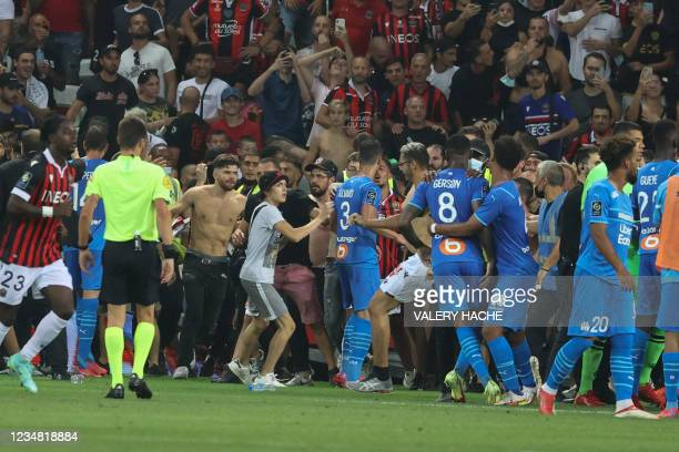 Fans invade the pitch during the French L1 football match between OGC Nice and Olympique de Marseille at the Allianz Riviera stadium in Nice,...