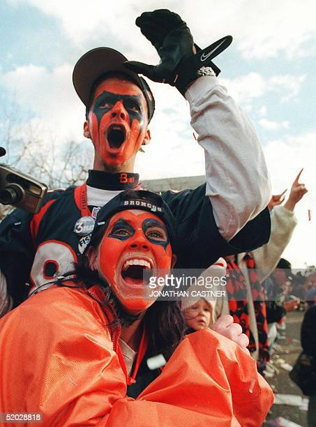 Fans Jennifer Donnelley of Greeley Colorado and Derek Cumings of Windsor Colorado cheer as the Super Bowl champion Denver Broncos approach in their...