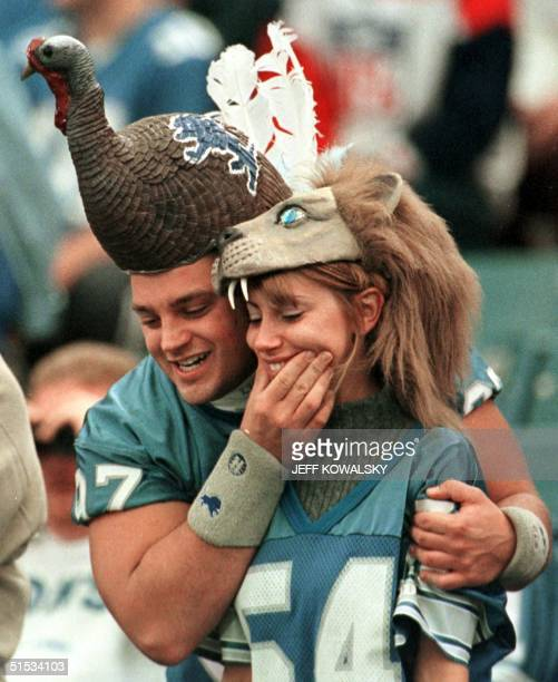 Fans Jerry Bac and Amy Cruc wear comical headgear before the start of the Chicago Bears Detroit Lions annual Thanksgiving Day game 25 November 1999...