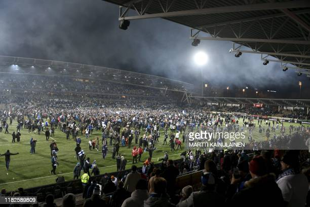 Fans join the players on the pitch to celebrate the victory after the UEFA Euro 2020 Group J qualification football match between Finland and...