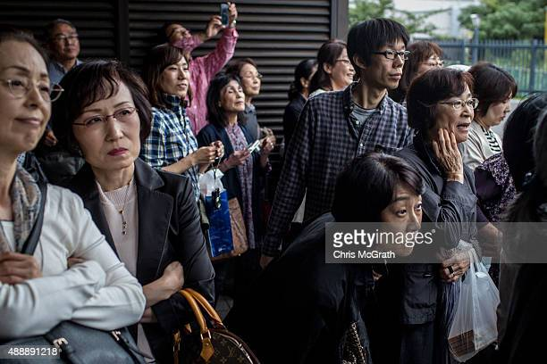 Fans jostle to get a glimpse of sumo wrestlers as the arrive for their fights during the Tokyo Grand Sumo tournament at the Ryogoku Kokugikan on...