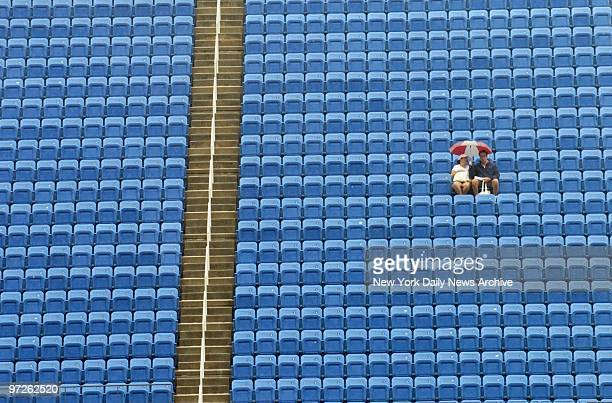 Fans keep a lonely vigil under their umbrella as they wait - and hope - for tennis matches, delayed by torrential rain, to get underway at the U.S....