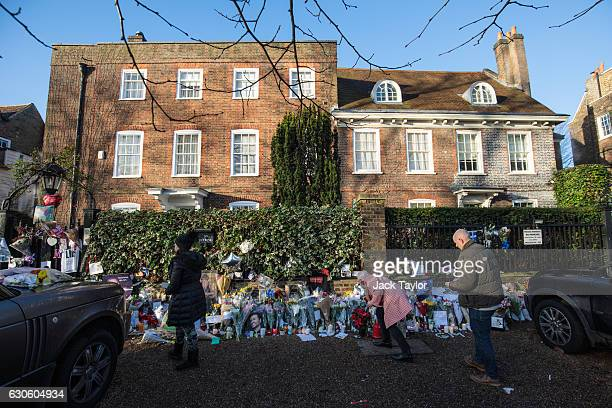 Fans lay tributes of flowers photographs and candles outside the home of pop music icon George Michael in The Grove Highgate on December 28 2016 in...