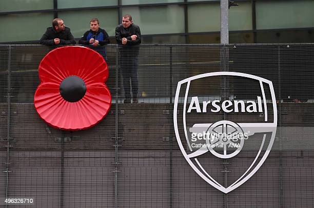 Fans lean over a giant poppy next to the Arsenal badge for remembrance day before the Barclays Premier League match between Arsenal and Tottenham...