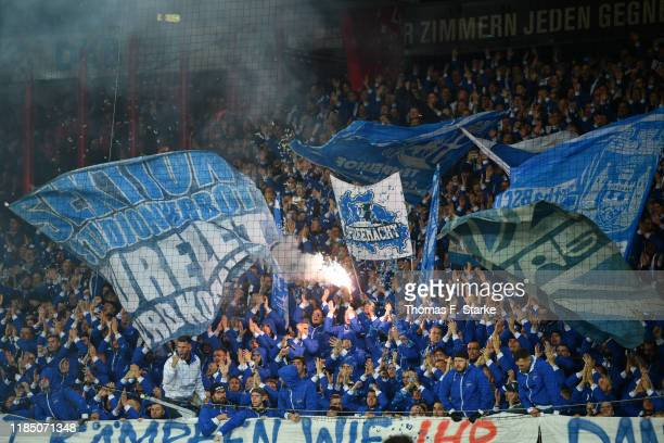 Fans let off a flare and wave flags prior to the Bundesliga match between 1. FC Union Berlin and Hertha BSC at Stadion An der Alten Foersterei on...