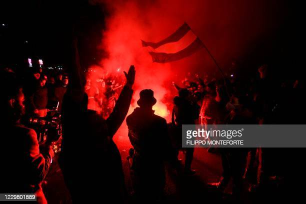 Fans light flare bombs and wave a flag of Argentina as people gather outside the San Paolo stadium in Naples on November 26, 2020 to mourn the death...