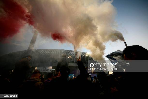 Fans light flare bombs as people gather outside the San Paolo stadium in Naples on November 26, 2020 to mourn the death of late Argentinian football...