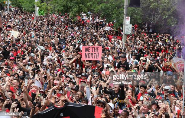 TORONTO ON JUNE 17 Fans line the route with signs as the Toronto Raptors hold their victory parade after beating the Golden State Warriors in the NBA...