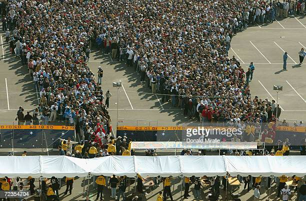 Fans line up for the security check point outside the stadium prior to the start of Super Bowl XXXVIII between the New England Patriots and the...