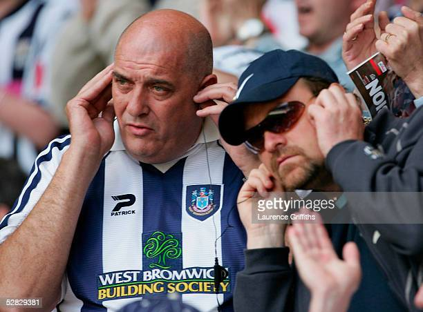 WBA fans listen to their radios during the Barclays Premiership match between West Bromwich Albion and Portsmouth at The Hawthorns on May 15 2005 in...