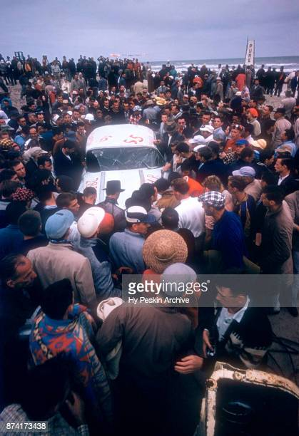 Fans look at Junior Johnson's wrecked Pontiac car after Johnson's car flipped multiple times during the Daytona Beach and Road Course on February 26...