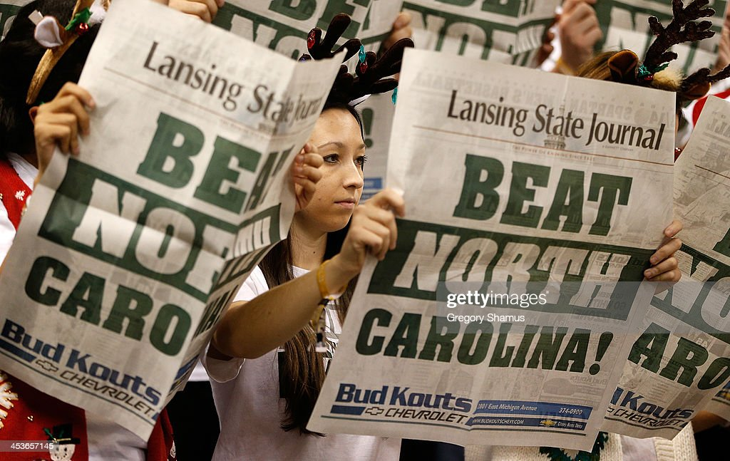 Fans look at newspapers while the North Carolina Tar Heels starting lineup is introduced prior to playing the Michigan State Spartans at the Jack T. Breslin Student Events Center on December 4, 2013 in East Lansing, Michigan. North Carolina won the game 79-65.