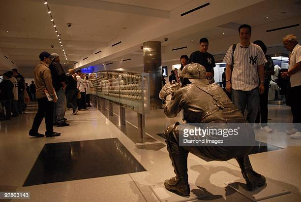 Fans look at the collection of autographed baseballs mounted within the case that stands under the arc of the path of the final pitch to catcher Yogi...