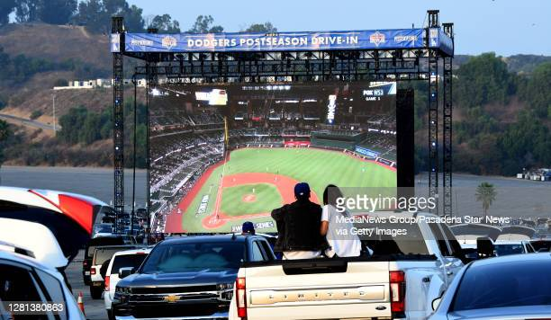 Fans look on a giant screen during game one of the World Series between the Tampa Bay Rays and the Los Angeles Dodgers in the parking lot of Dodger...