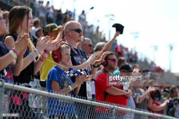 Fans look on and cheer during the NASCAR XFINITY Series Sports Clips Haircuts VFW 200 at Darlington Raceway on September 2 2017 in Darlington South...