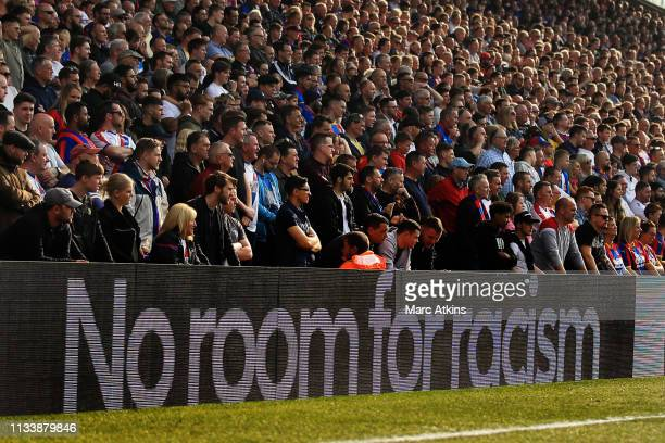 Fans look on as an anti racism message is shown on the advertising boards during the Premier League match between Crystal Palace and Huddersfield...