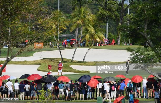 Fans look on as Ariya Jutanugarn of Thailand Minjee Lee of Australia and Jodi Ewart Shadoff of England putt on the first green during the final round...