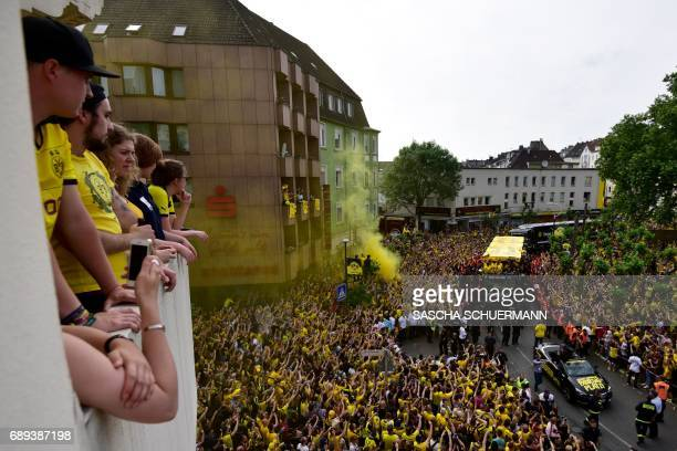 Fans look on as Borussia Dortmund players arrive at Borsigplatz during celebrations after winning the German Cup final in Dortmund western Germany on...