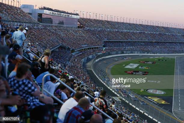 Fans look on as cars race during the Monster Energy NASCAR Cup Series 59th Annual Coke Zero 400 Powered By CocaCola at Daytona International Speedway...