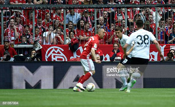 Fans look on as Franck Ribery of Muenchen is challenged by Fynn Arkenberg of Hannover during the Bundesliga match between FC Bayern Muenchen and...