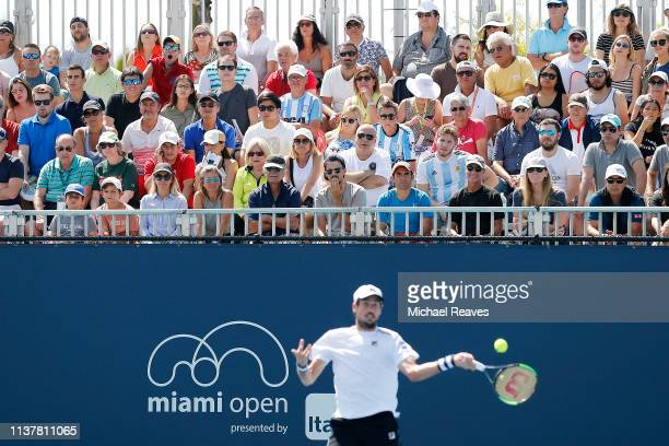 Fans look on as Guido Pella of Argentina returns a shot to Leonardo Mayer of Argentina on Day 6 of the Miami Open Presented by Itau at Hard Rock...