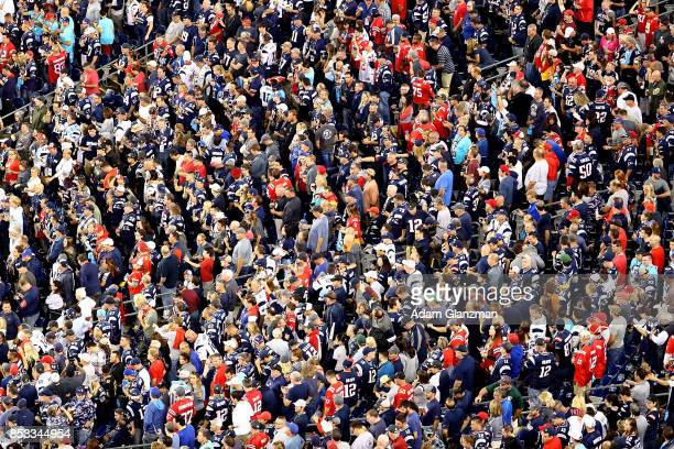 Fans look on as New England Patriots Super Bowl Championship banners and an American flag are displayed on the field during the national anthem prior...