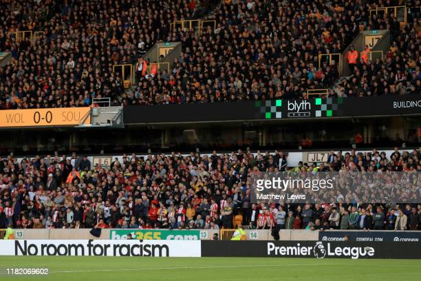 Fans look on as No Room for Racism branding is seen on the advertising boards during the Premier League match between Wolverhampton Wanderers and...