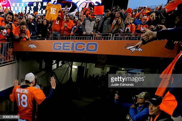 Fans look on as Peyton Manning of the Denver Broncos walks off the field after defeating the New England Patriots in the AFC Championship game at...