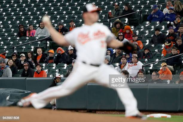 Fans look on as starting pitcher Dylan Bundy of the Baltimore Orioles throws to a Toronto Blue Jays batter in the first inning at Oriole Park at...