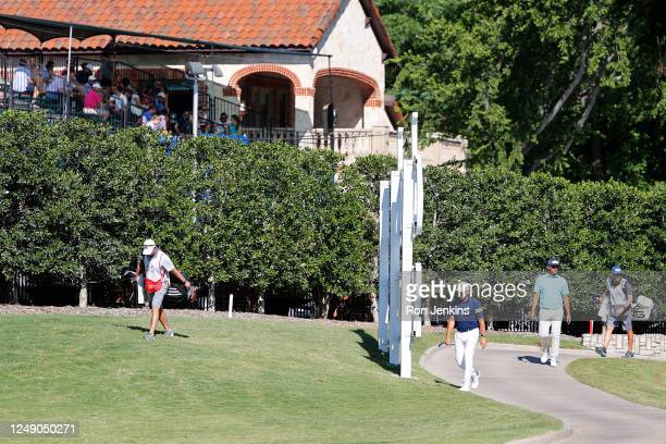 Fans look on from a grandstand setup in the yard of a neighboring property as Sergio Garcia of Spain walks past during the first round of the Charles...