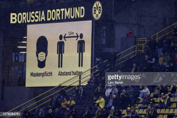 Fans look on from the stands as a screen in the stadium asks fans to wear face masks and to respect social distancing guidlines during the Bundesliga...